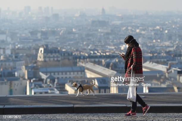 A woman wearing a protective mask walks her dog on the third day after the announcement by French President Emmanuel Macron of the confinement of the...