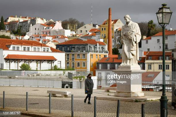 Woman wearing a protective mask walks near the St. Vincent monument in Graça. According to a report from the General Health Department , Portugal has...
