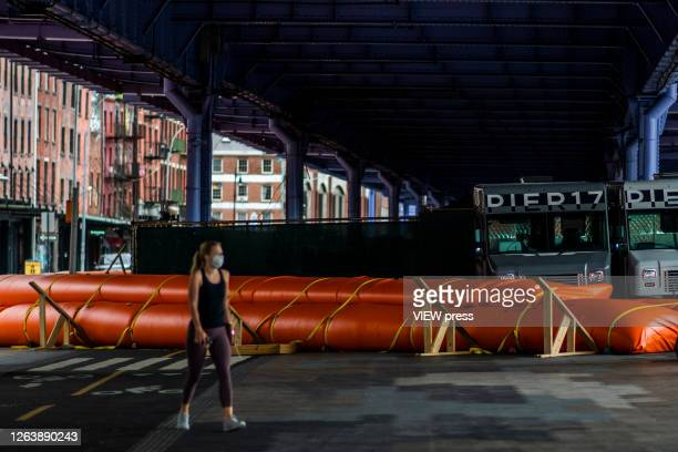 A woman wearing a protective mask walks next to flood barriers used to prevent flooding at the South Street Seaport as the city gets ready for...