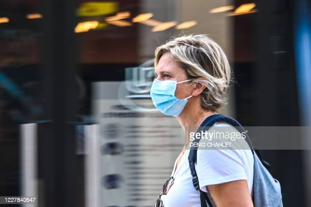 Woman wearing a protective mask walks on a street in Lille, northern France, on July 30 as The Nord Prefecture announced, the reinforcement of the...