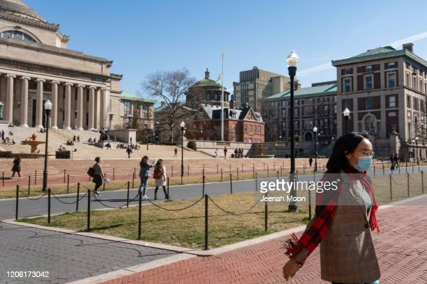 A woman wearing a protective mask walks on the Columbia University campus on March 9 2020 in New York City The university is canceling classes for...