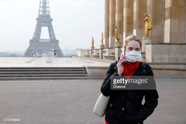 A woman wearing a protective mask walks on the Esplanade du Trocadero square in front of the Eiffel Tower the second day after the announcement by...