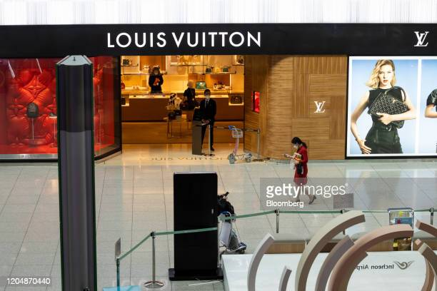 Woman wearing a protective mask walks past a Louis Vuitton store, a unit of LVMH Moet Hennessy Louis Vuitton SA, in the duty free shopping area at...