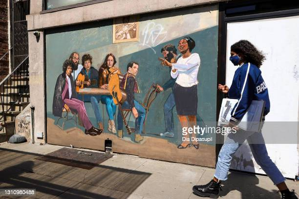 "Woman wearing a protective mask walks past a mural titled ""Spirit of Greenwich Village"" by Amer Olson featuring Jimi Hendrix, Allen Ginsberg, Bob..."