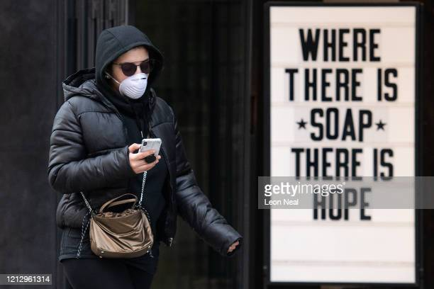 A woman wearing a protective mask walks past a sign in a cosmetic shop window on March 17 2020 in London England Boris Johnson held the first of his...