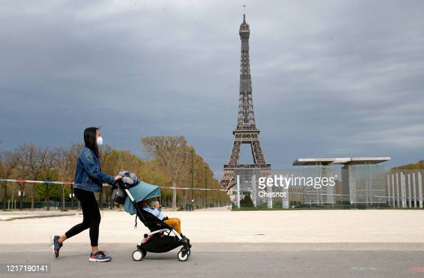 Woman wearing a protective mask with a child in a stroller walks past next to the Eiffel Tower during the coronavirus epidemic on April 6 in Paris,...
