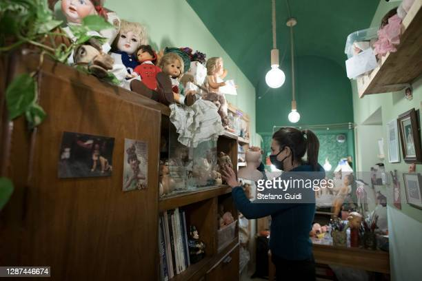 A woman wearing a protective mask works inside her doll restoration shop in Via Barbaroux on November 24 2020 in Turin Italy Via Barbaroux is an old...