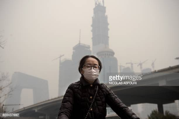 A woman wearing a protective pollution mask rides a bicycle in Beijing on March 20 2017 The last large coalfired power plant in Beijing has suspended...