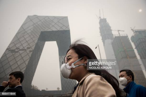 A woman wearing a protective pollution mask walks on a street in Beijing on March 20 2017 The last large coalfired power plant in Beijing has...