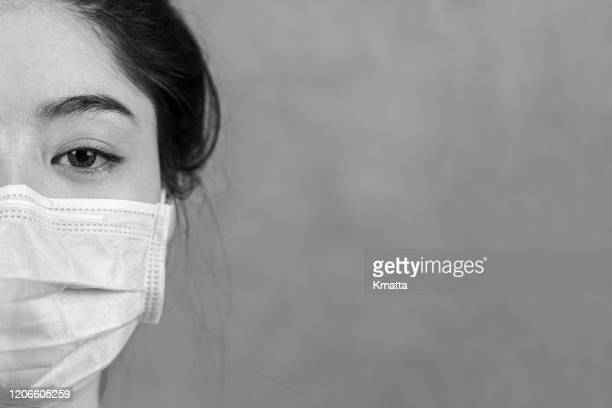 a woman wearing a protective surgical mask. - nurse mask stock pictures, royalty-free photos & images