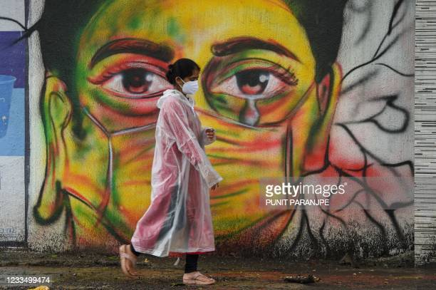 Woman wearing a raincoat walks past a mural depicting a woman with a facemask to spread awareness about the Covid-19 coronavirus, in Mumbai on June...