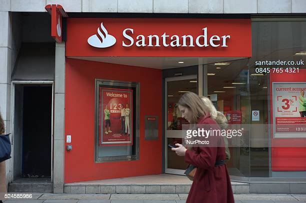 A woman wearing a red coat and using a mobile phone on Thursday 13th November 2014 walks by a branch of Santander UK in central Manchester Santander...