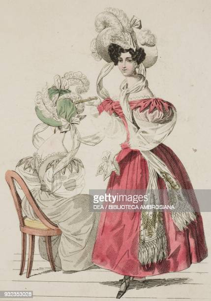 Woman wearing a red dress with puffed sleeves white hat adorned with ribbons and feathers and a woman wearing the same outfit in lighter tones and...