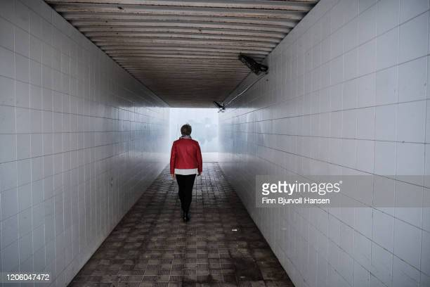 woman wearing a red jacket walking in a tunnel - finn bjurvoll stock pictures, royalty-free photos & images