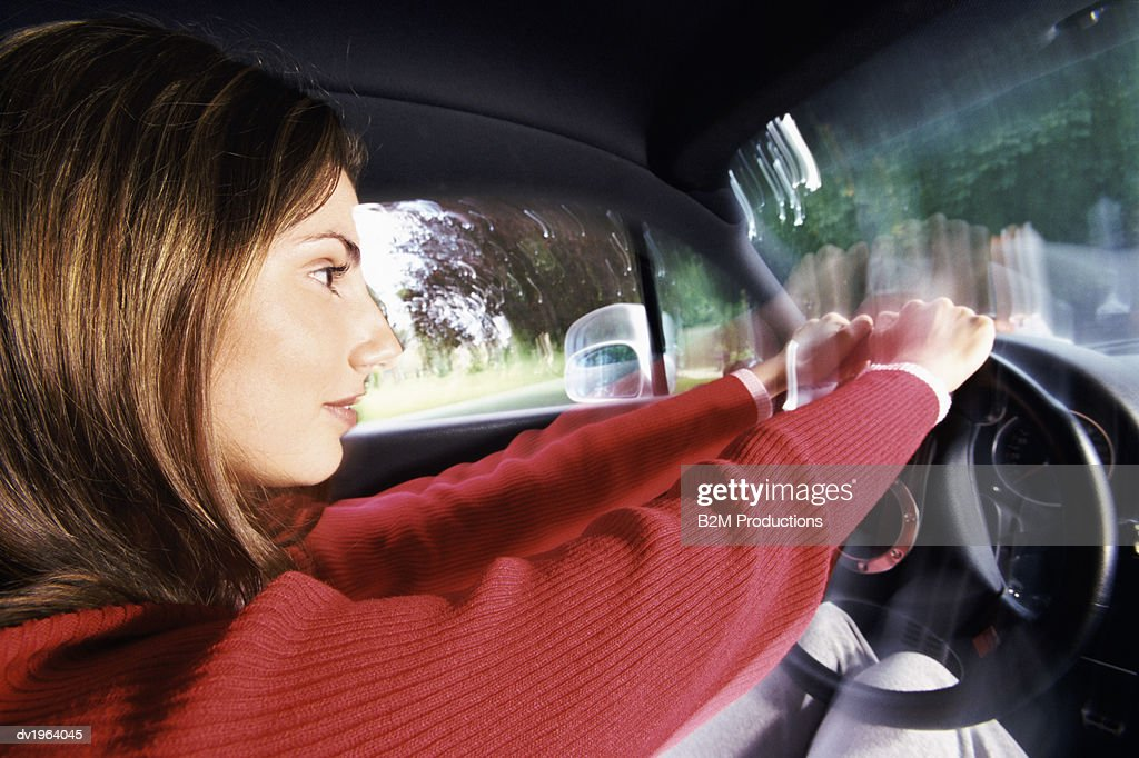 Woman Wearing a Red Jumper Driving a Car : Stock Photo