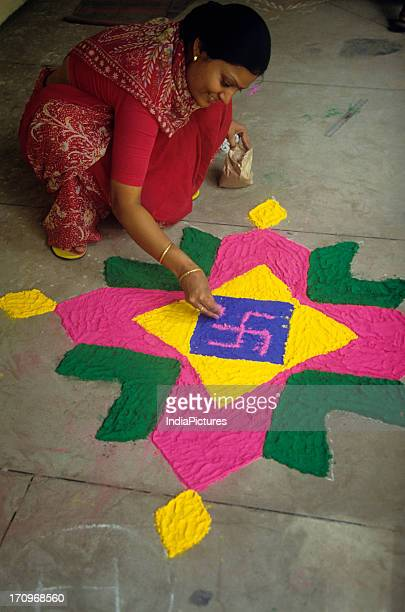 A woman wearing a red suit is making a rangoli in her house during a festive season India