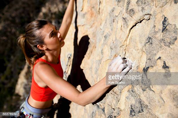 a woman wearing a red tank top and striped pants climbs the rapture (5.8) on lower gibraltar rock in santa barbara, california. - lady barbara stock-fotos und bilder