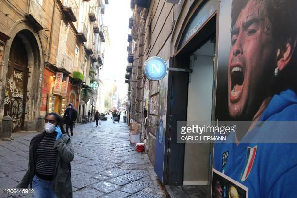 A woman wearing a respiratory mask as part of precautionary measures against the spread of the new COVID19 coronavirus walks past a poster of...