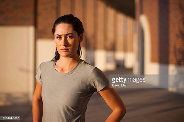 a woman wearing a running shirt stands in front of a series of columns. - columnata fotografías e imágenes de stock