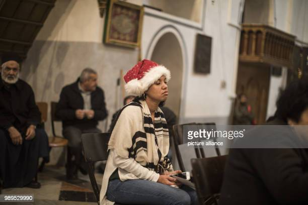 Woman wearing a Santa Claus hat and the typical Jewish praying shawl 'Talit' reacts as she attends Christmas prayers in the Church of the Nativity,...