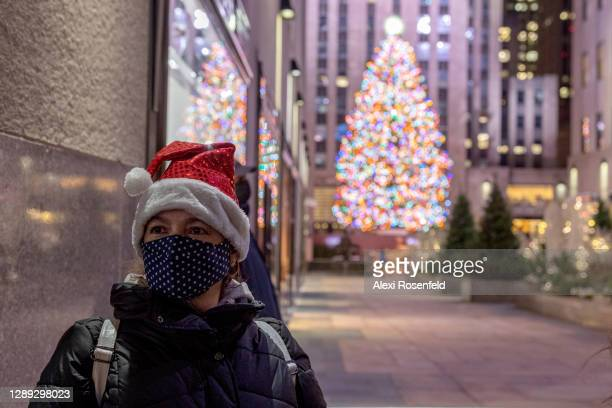 Woman wearing a Santa Claus hat poses in front of the newly lit Christmas Tree in Rockefeller Center on December 03, 2020 in New York City.
