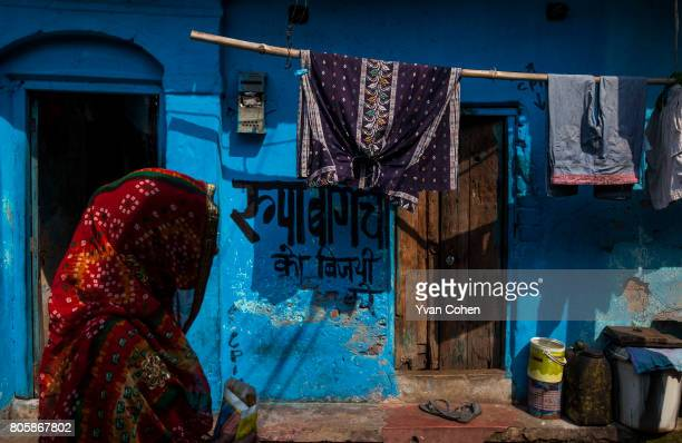 A woman wearing a saree walks past a bright blue wall in Kolkata The capital of the Indian state of West Bengal Kolkata is one of India's most...