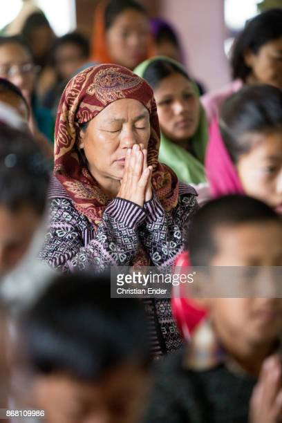 A woman wearing a sari is praying with closed eyes while a ceremony inside a church in Kalimpong