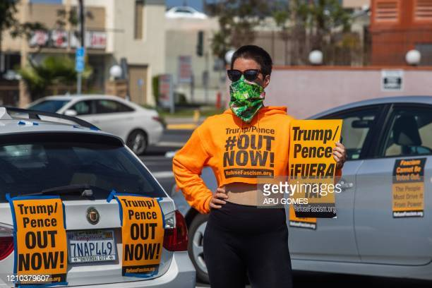 A woman wearing a scarf as a preventive measure against the spread of COVID19 holds a sign during an antiTrump protest where demonstrators delivered...