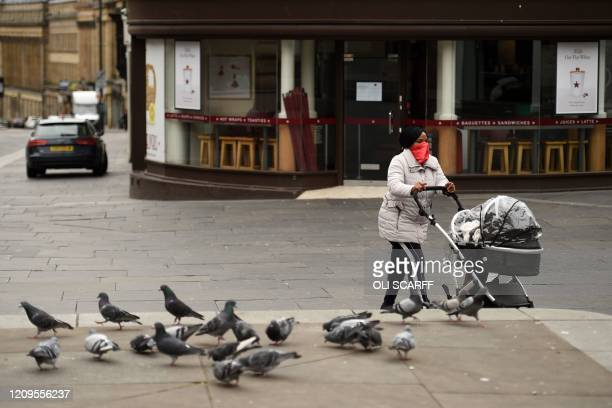 Woman wearing a scarf as a protective face mask, pushes a pram through the centre of Newcastle upon Tyne, Thursday lunchtime in north-east England on...