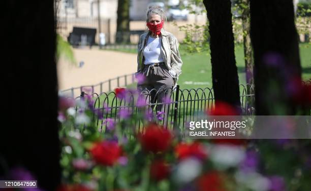A woman wearing a scarf as PPE fashioned into face mask as a precautionary measure against COVID19 walk past spring flowers in central London as...