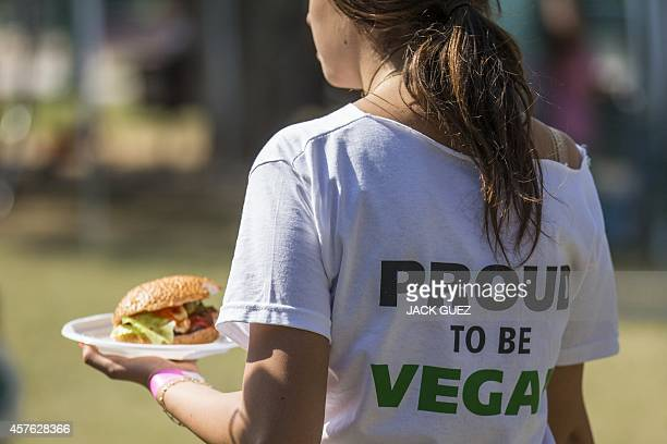 """Woman, wearing a shirt reading """"proud to be vegan"""", carries a vegan hamburger during the """"Vegan Fest"""" fair on October 13, 2014 in the Israeli city of..."""
