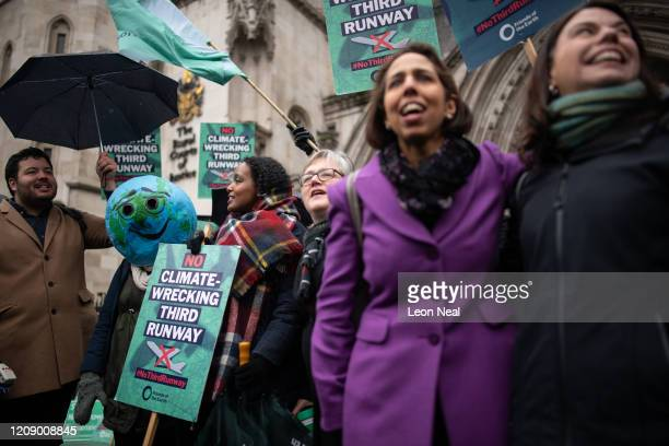 A woman wearing a smiling earth mask celebrates as she stands with fellow campaigners outside the Royal Courts of Justice following the announcement...