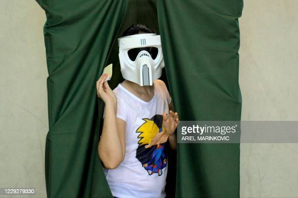 Woman wearing a Star Wars Stormtrooper mask prepares to cast her ballot during a constitutional referendum voting at a polling station in Santiago,...
