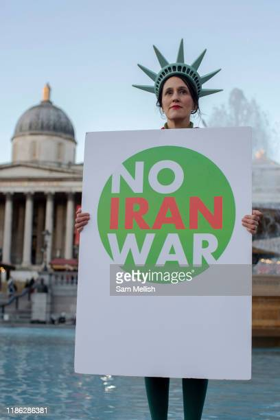 Woman wearing a Statue of Liberty hat whilst holding a sign saying 'No Iran War' during a protest against U.S. President Donald Trump UK visit to...