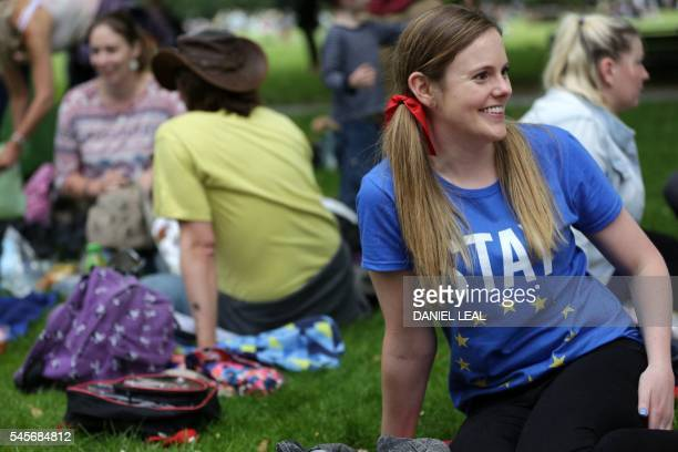 A woman wearing a 'Stay' Tshirt smiles during a picnic against Brexit organised by the General Assembly in Green Park in London on July 9 2016 The...
