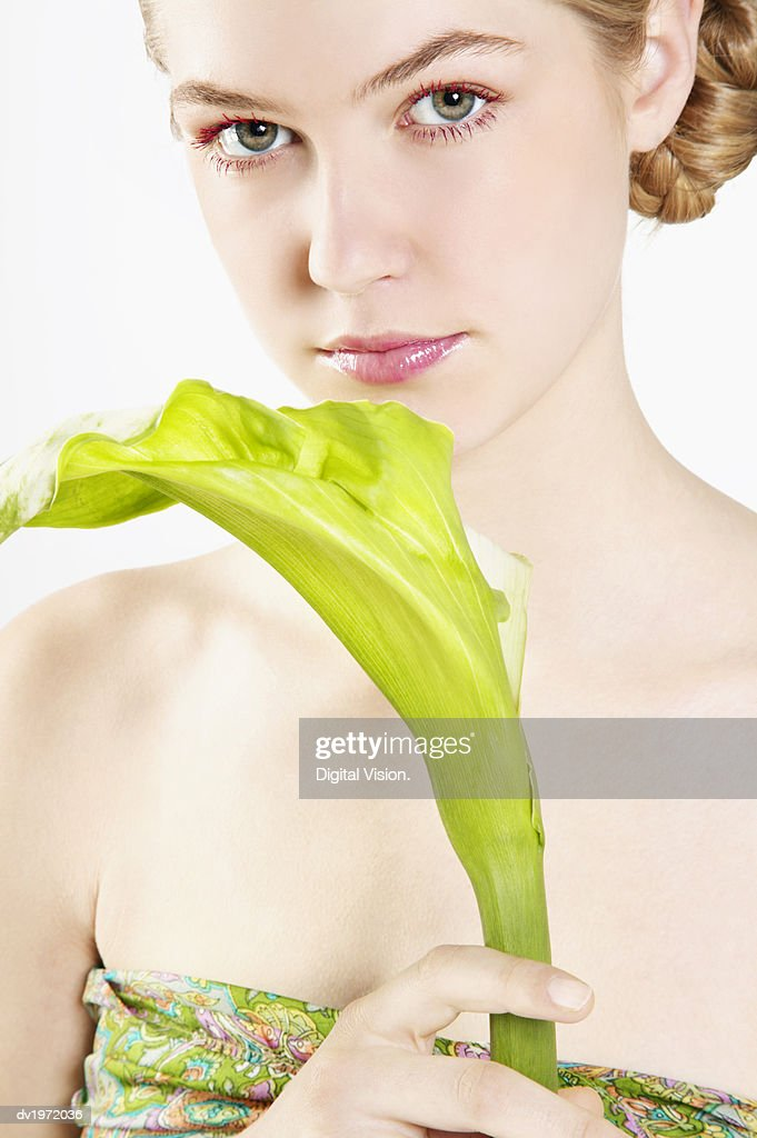 Woman Wearing a Strapless Top Holding a Green Leaf : Stock Photo