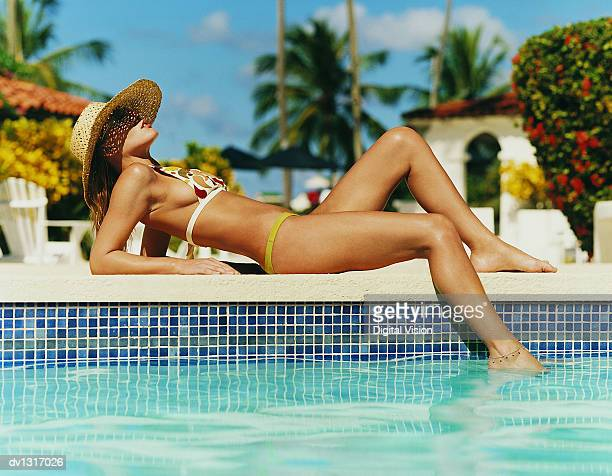 Woman Wearing a Straw Hat Sunbathing at the Edge of a Swimming Pool