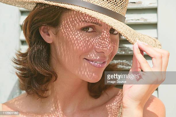 Woman wearing a sun hat with shadows on face