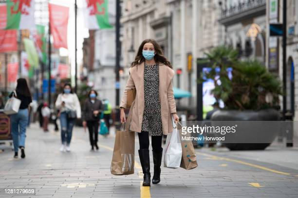 Woman wearing a surgical face mask carries bags of shopping on St. Mary Street on October 20, 2020 in Cardiff, Wales. Wales will go into a national...