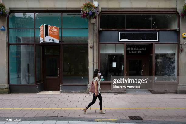Woman wearing a surgical face mask walks passed closed shops on Queen Street on August 4, 2020 in Cardiff, United Kingdom. Coronavirus lockdown...