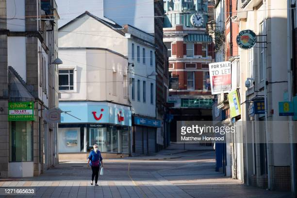 Woman wearing a surgical face mask walks through the town centre on September 9, 2020 in Merthyr Tydfil, Wales. In the past week 6% of coronavirus...