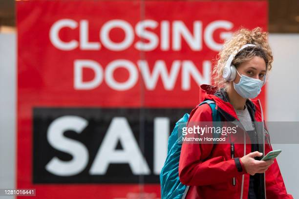 Woman wearing a surgical face mask while wearing headphones and holding a mobile phone walks past a shop with a closing down sign in the window on...