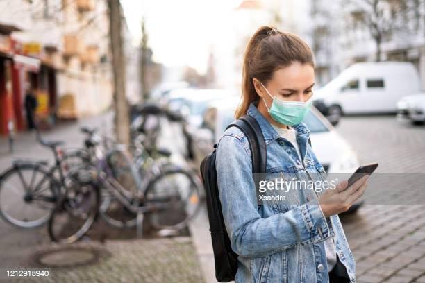 frau trägt eine chirurgische maske und mit einem telefon im freien - grippeschutzmaske stock-fotos und bilder