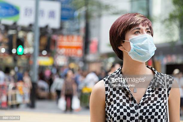 woman wearing a surgical mask in hong kong - surgical mask stock pictures, royalty-free photos & images