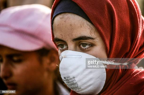 TOPSHOT A woman wearing a surgical mask looks on during a demonstration by Palestinian women along the border with Israel east of Gaza City on July 3...
