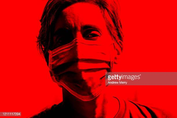 woman wearing a surgical mask, protective face mask against infectious diseases like coronavirus, covid-19 and influenza - covid 19 stock-fotos und bilder