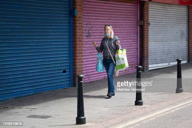A woman wearing a surgical mask walks passed closed shops carrying shopping bags during the coronavirus lockdown period on June 13 2020 in Barry...