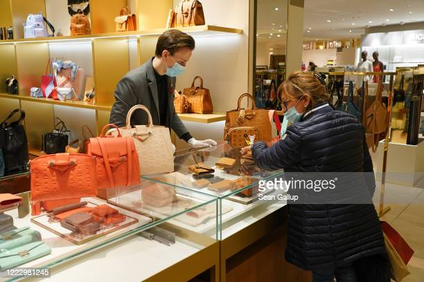Woman wearing a surgical mask who said she did not mind being photographed shops at a counter of luxury handbags at the KaDeWe department store on...