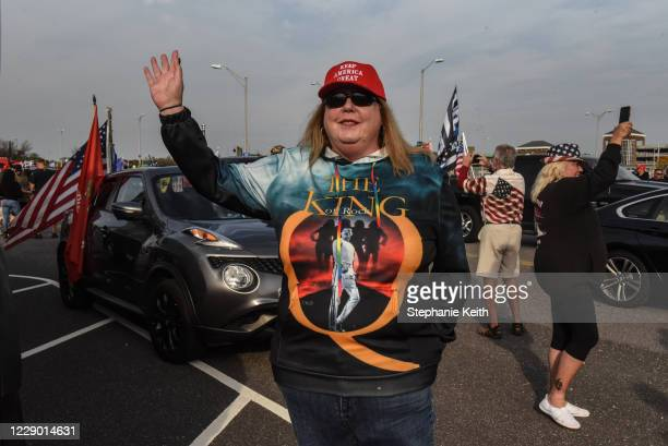 Woman wearing a sweatshirt for the QAnon conspiracy theory gestures during a pro-Trump rally on October 11, 2020 in Ronkonkoma, New York. With...