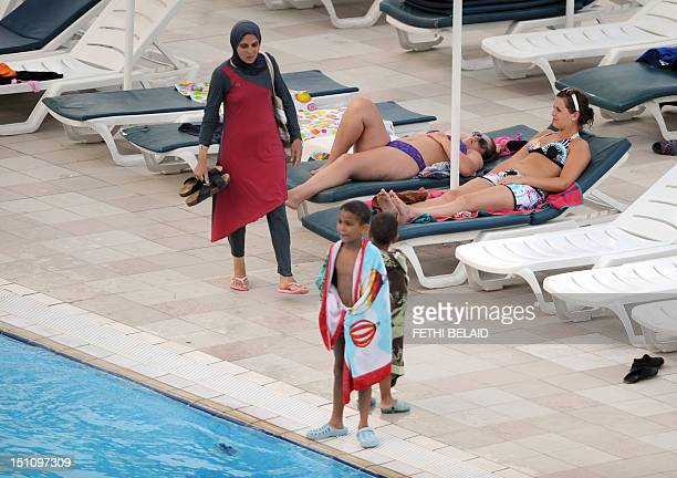 A woman wearing a swimming outfit or burkini that covers her body walks past women wearing bikinis at the pool of a hotel in the Tunisian coastal...